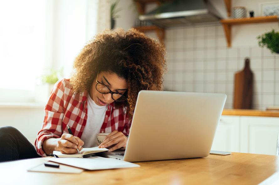 mulher anotando estratégias de estudo no papel após pesquisar no notebook