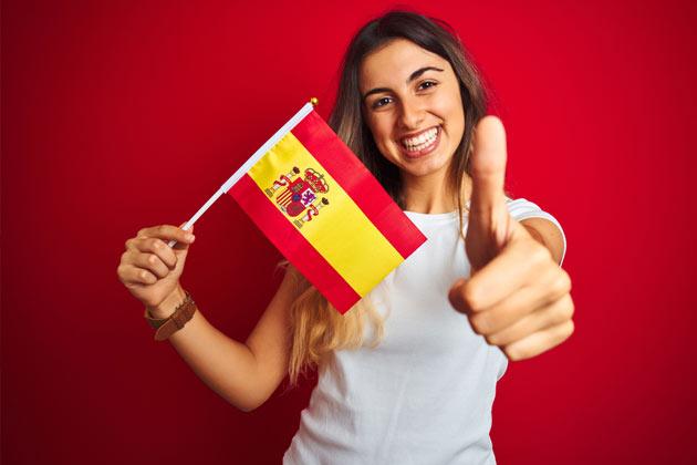 mulher em fundo vermelha segurando bandeira da espanha
