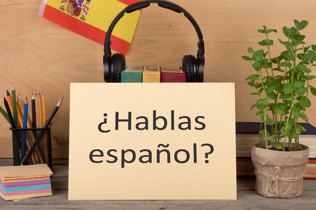Placa com pergunta em espanhol e fone de ouvido